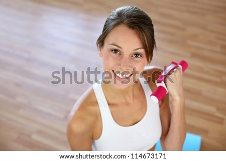 Fitness girl lifting dumbbells in gym - stock photo