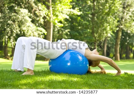 Fitness girl outdoor exercise by Pilate ball. - stock photo