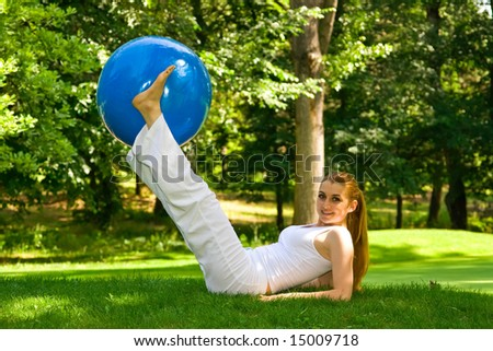 Fitness girl outdoor exercise by pilates ball. - stock photo