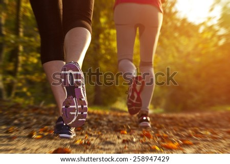 Fitness Girl running at sunset in forest - stock photo