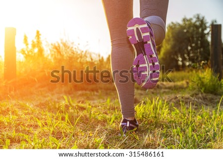 Fitness Girl running in a field with colorful outfit