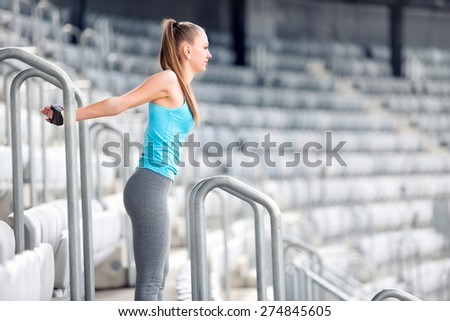 Fitness girl stretching and doing gymnastics exercises on stadium stairs. Athlete girl and people working out concept - stock photo