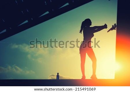 Fitness girl training in sunny sunshine, beautiful woman doing sports outdoors, attractive female runner stretching before her workout on beautiful background of sunset sky, woman fitness silhouette - stock photo