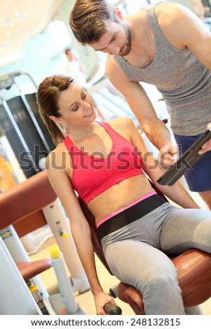 Fitness girl with coach setting up program - stock photo