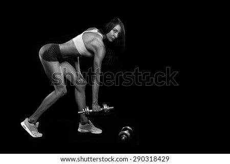 Fitness girl with dumbbells on a black background