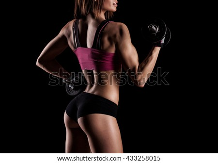 Fitness girl with dumbbells on a dark background - stock photo
