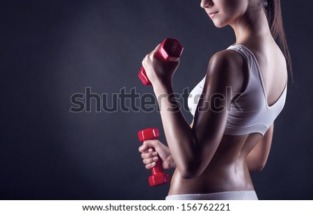 Fitness girl with dumbbells on a dark background. Back view - stock photo