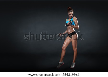 Fitness girl with dumbbells on a dark background isolated with clipping path - stock photo
