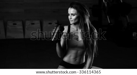 Fitness girl with shaker relaxing in the gym - stock photo
