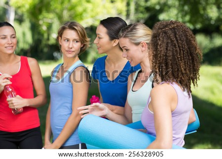 Fitness group chatting in park on a sunny day - stock photo