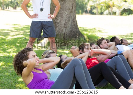 Fitness group doing sit ups in park with coach on a sunny day - stock photo