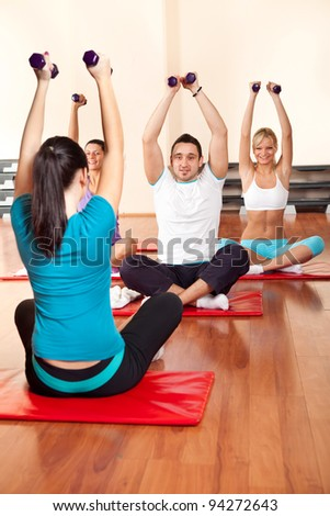 fitness group exercising with dumbbells and looking in instructor