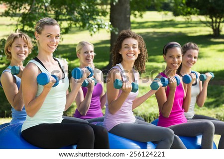 Fitness group lifting hand weights in park on a sunny day - stock photo