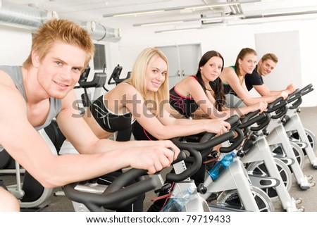 Fitness group of people on bicycle at gym - stock photo
