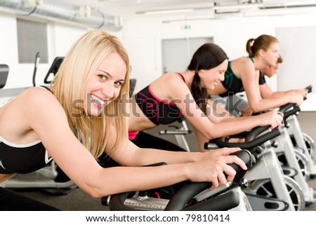 Fitness group of people on bicycle at gym