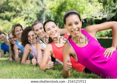 Fitness group planking in park on a sunny day - stock photo