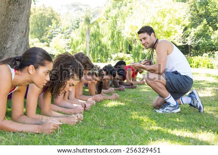Fitness group planking in park with coach on a sunny day - stock photo