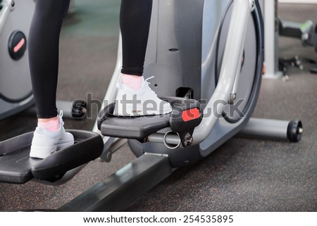 Fitness gym workout. Cropped image of young beautiful woman in sports clothing doing exercises in the gym on elliptical cross trainer - stock photo