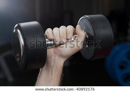Fitness hall. The hand holds dumbbells. Close-up - stock photo