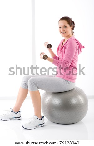 Fitness happy tired woman exercise dumbbell ball on white - stock photo