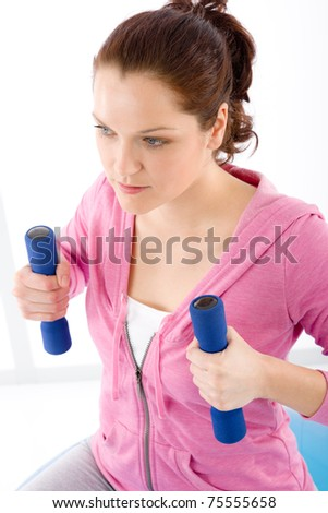Fitness happy woman exercise with dumbbell on white - stock photo