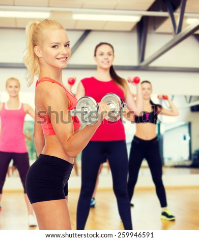 fitness, healthcare and exercise concept - young sporty woman with heavy steel dumbbell - stock photo