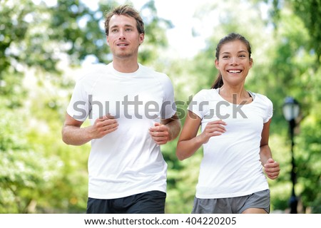 Fitness healthy lifestyle. Happy couple running summer training for marathon in Central Park Manhattan, New York. Asian female model and Caucasian sport fitness male athlete enjoying jogging together. - stock photo
