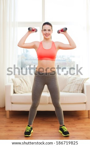 fitness, home and diet concept - smiling redhead girl exercising with heavy dumbbells at home - stock photo