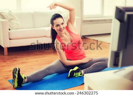 fitness, home and diet concept - smiling teenage girl stretching on floor and watching tv at home - stock photo