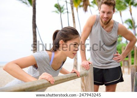 Fitness instructor coaching and helping woman doing push-ups on cross fit horizontal bar station on beach. Arm press pushups easy exercises. - stock photo