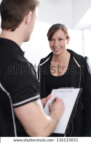 Fitness Instructor interviewing new client in gym - stock photo