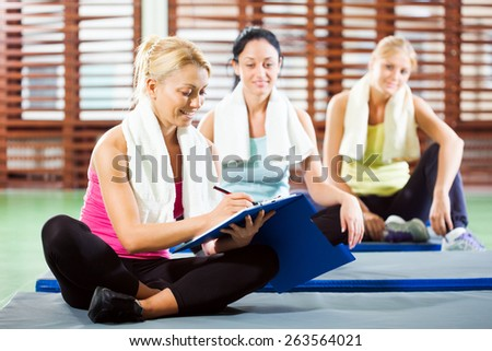 Fitness instructor is making plan for exercise - stock photo