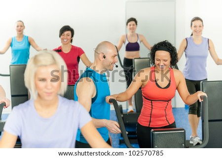 Fitness instructor leading class of alpinning at the gym - stock photo