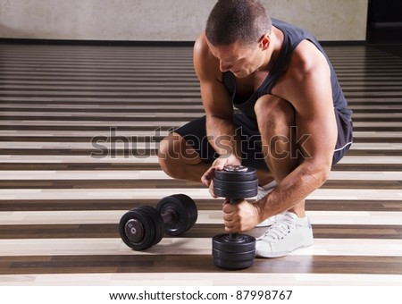 Fitness instructor setting up his weights for weightlifting