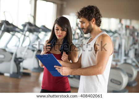 Fitness instructor showing a training schedule to a woman - stock photo