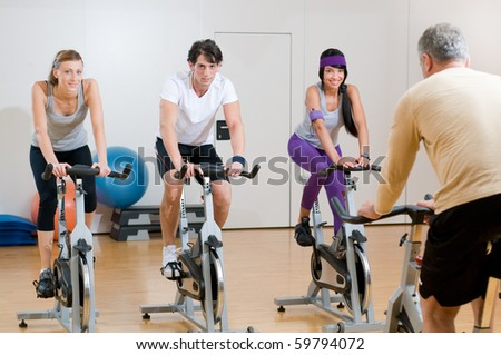 Fitness instructor with his class of cycler at gym - stock photo