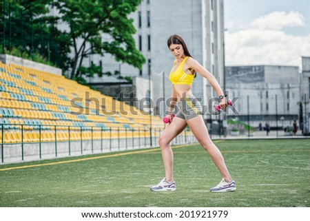 Fitness load with dumbbells. Young woman doing fitness training on the football field on the street - stock photo