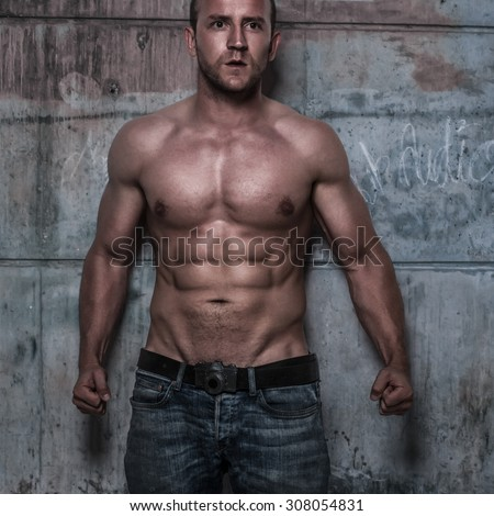 fitness male model with sixpack on the rustic wall - stock photo