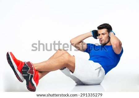 Fitness man doing abdominal exercises isolated on a white background - stock photo