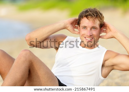 Fitness man doing crunches sit-ups on beach  - stock photo