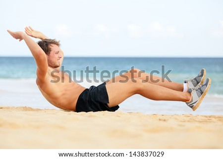 Fitness man doing crunches sit-ups on beach exercise outside. Fit male athlete exercising sit ups training on beautiful beach. Handsome sport model in cross training workout outdoors. - stock photo