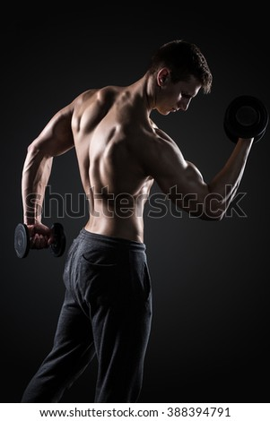 Fitness man doing exercises with dumbbells at biceps, rear view