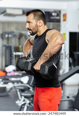 Fitness man doing shoulder workout with dumbbells in a gym - stock photo