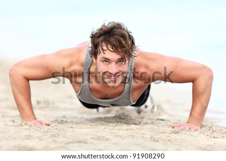 fitness man exercising push ups smiling happy. Male fitness model cross-training on beach. Caucasian man in his twenties. - stock photo