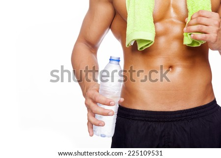 Fitness man holding a bottle of water, isolated on white background - stock photo