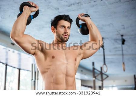 Fitness man lifting kettle ball - stock photo