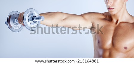 Fitness man lifting weights on gray background - stock photo