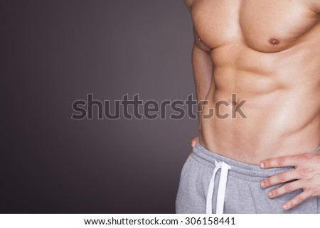 Fitness man showing six pack abs on grey background - stock photo