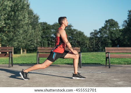 Fitness man stretching legs before outdoor workout. Sporty male athlete in an urban park warming up.