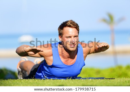 Fitness man training back extension exercise outdoor. Fit male sport athlete exercising lower back during cross training workout outside on grass in summer. Fit handsome muscular sports model. - stock photo